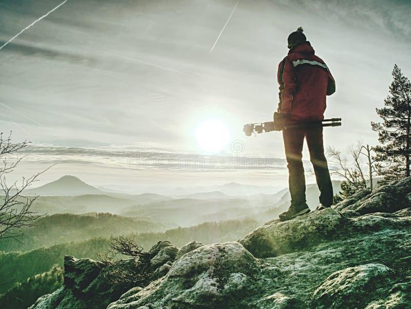 Man hold tripod. Hiker admiring stunning mountain range royalty free stock photography