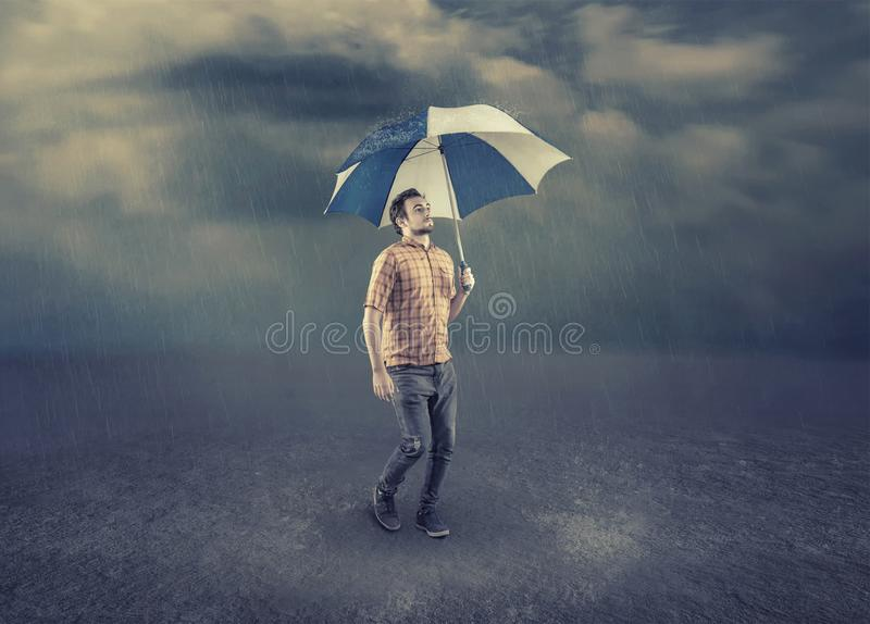 Young man holding an umbrella. Man hold an umbrella while walk on a rainy day royalty free stock image