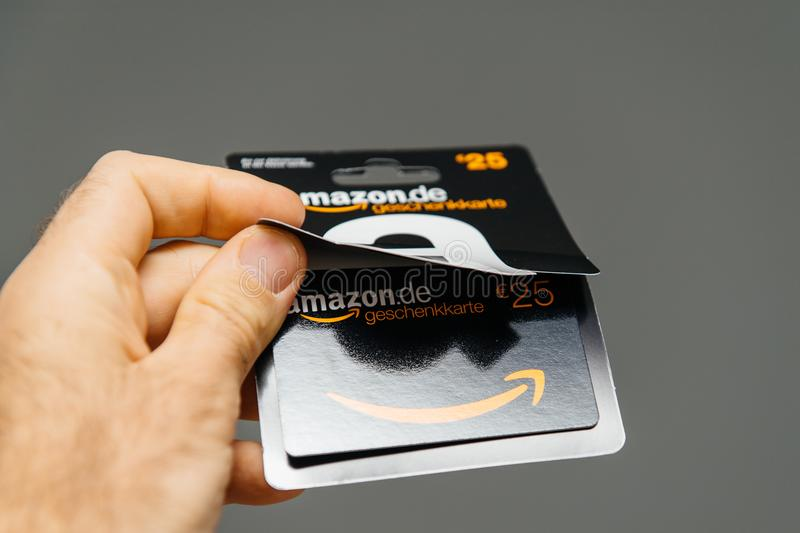 Man holding against gray background 25 Euros Amazon gift card is. PARIS, FRANCE - APR 1, 2018: Man opening 25 Euros Amazon gift card issued by Amazon Germany royalty free stock image