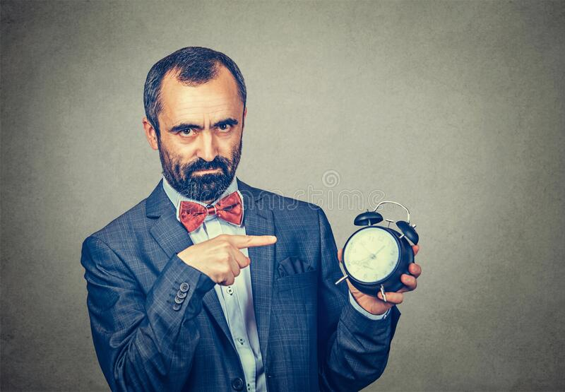 Man holding alarm clock and pointed it out. Closeup portrait serious angry annoyed frustrated adult bearded man in elegant jacket with red bow tie holding alarm stock photography