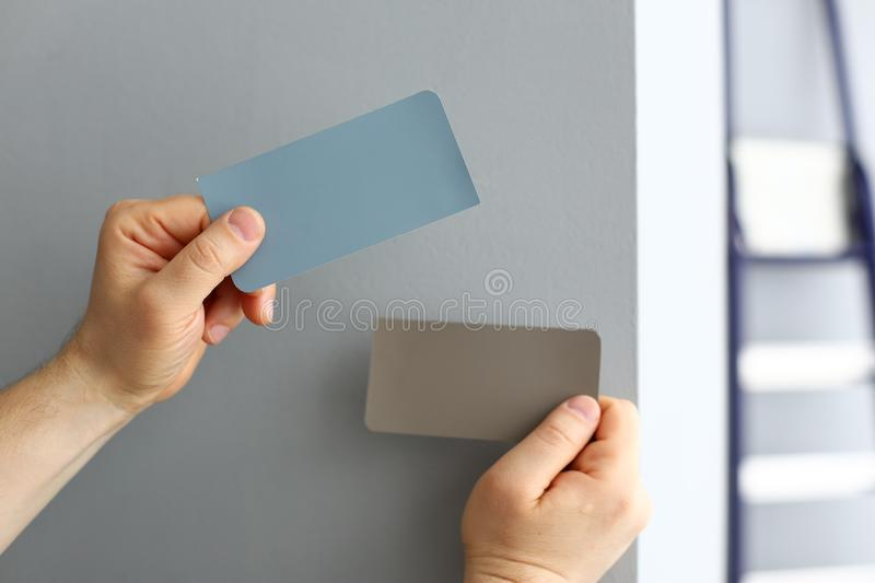 Man holding in arms colour palettes while choosing new paint for house stock photo