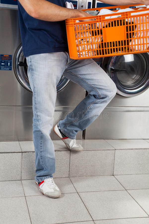 Man Holding Basket Of Clothes In Laundry royalty free stock image