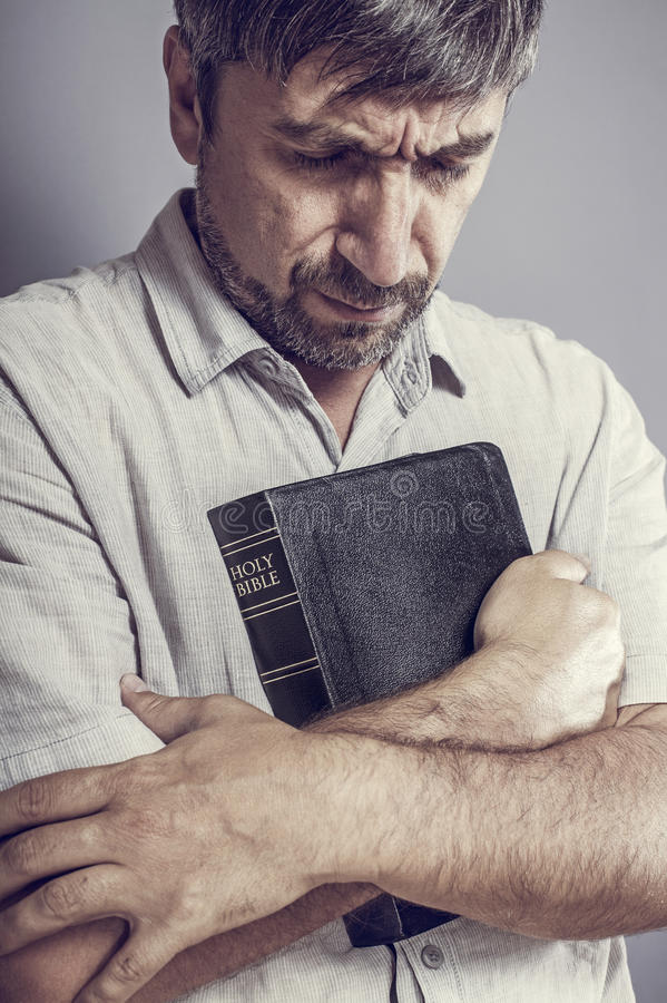 Man holding a bible. And praying royalty free stock image