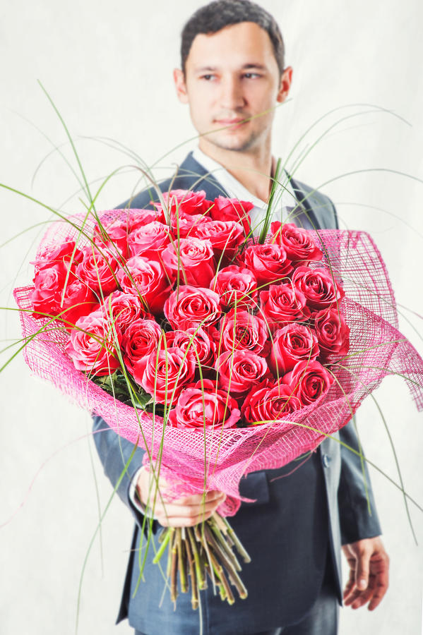 Man holding big bunch of red roses royalty free stock photography