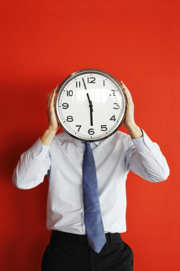 Man holding big clock covering face stock images