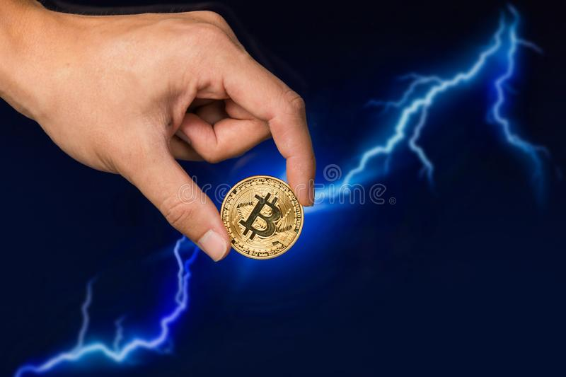 Bitcoin coin in front of lightning. Man holding Bitcoin gold coin in front of lightning network concept background royalty free stock photo