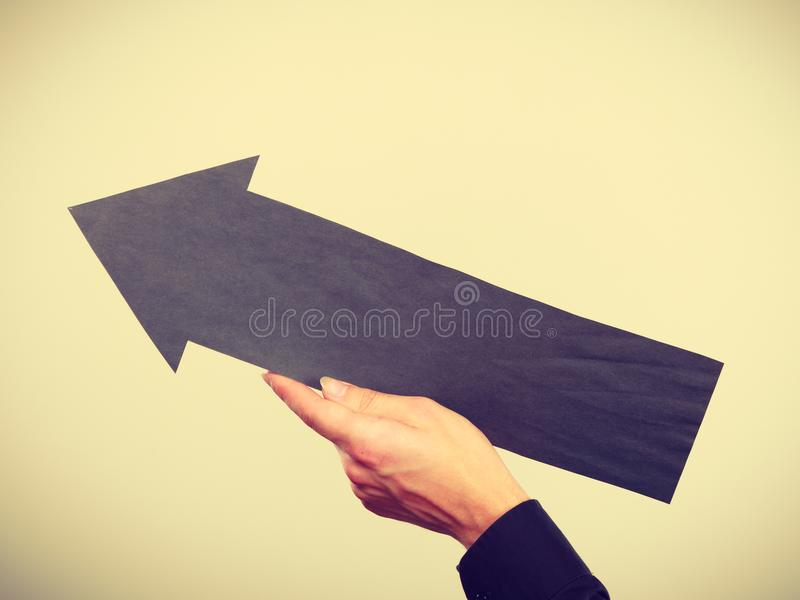 Man holding black arrow pointing left up royalty free stock images