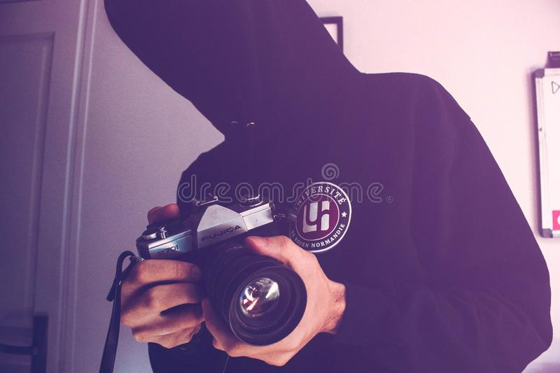 Man Holding Black and Gray Dslr Camera Inside White Wall Paint Room stock photos