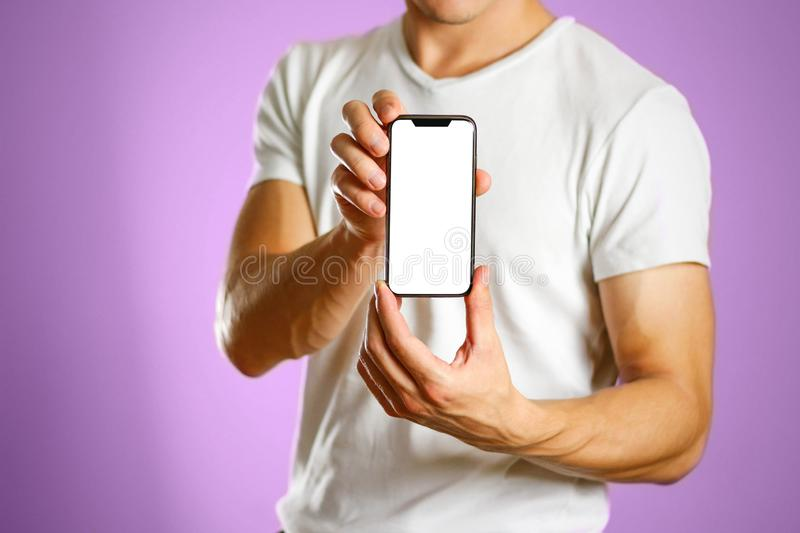 A man holding a black smartphone with a white blank screen. Smartphone with large screen. Close up. Isolated background royalty free stock photography
