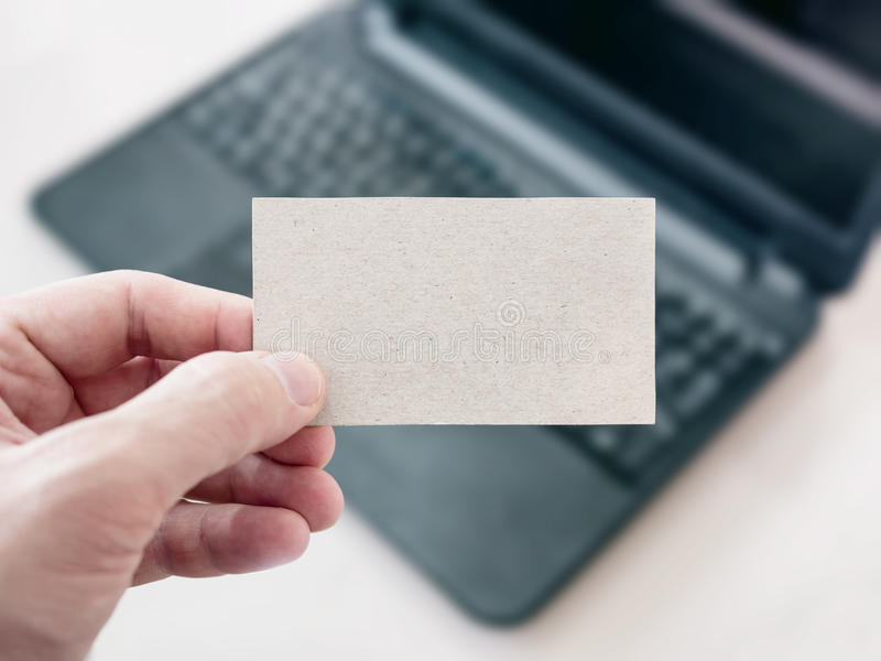 Man Holding A Blank Cardboard Business Card And Using Laptop Stock ...