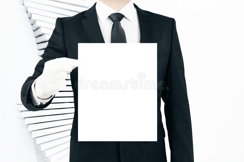 Man holding blank poster. Businessman holding blank white poster on light baclground. Business concept. Mock up royalty free stock photography