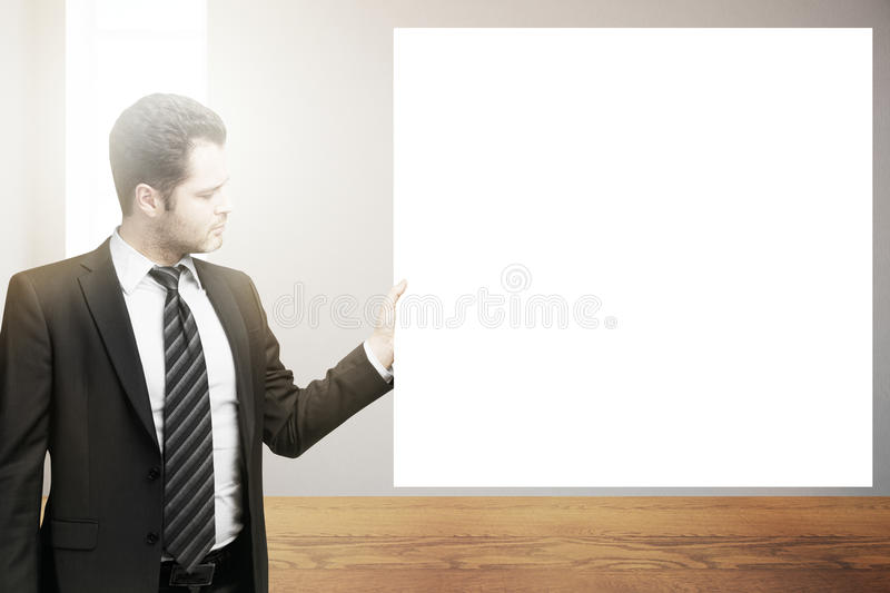 Man holding blank poster. Handsome young businessman in suit and tie holding blank poster in interior. Mock up royalty free stock photography