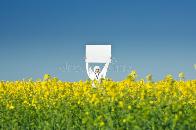 Man holding blank sign. A view of a man standing in a field of yellow flowers, holding a large blank sign while wearing a white jumpsuit and carrying a large stock photos
