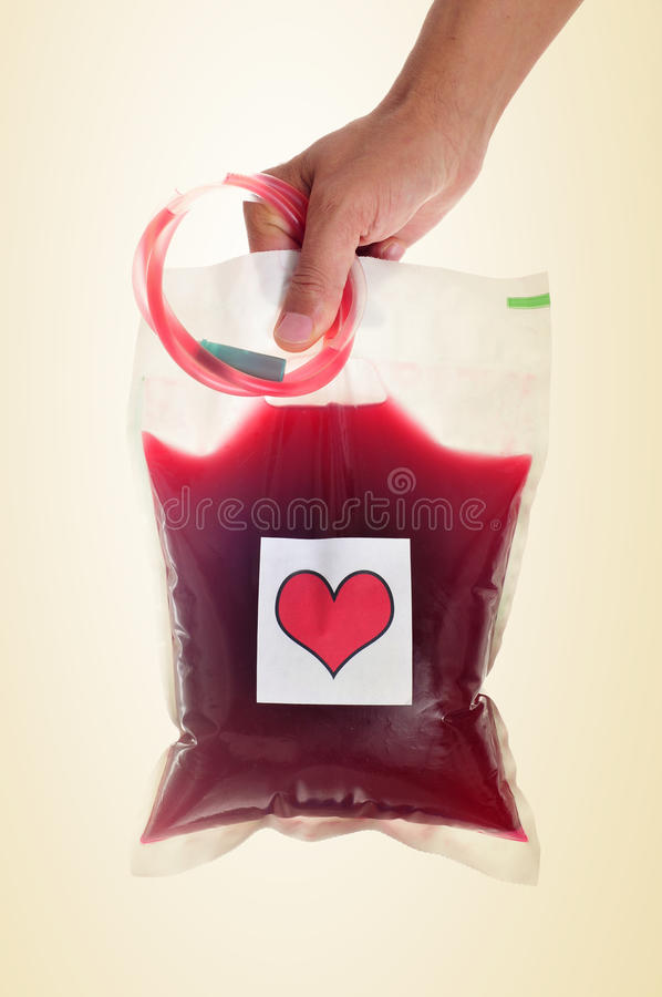 Man holding a blood bag with a sticker of a red heart stock photos