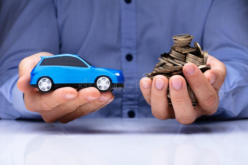 Man Holding Blue Car And Golden Coins stock photo