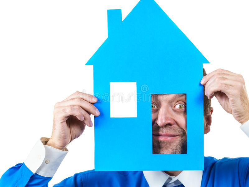 Man holding blue house model. Man holding blue conceptual house model. Real estate agent, home ownership concept. Studio shot on white isolated background stock photography