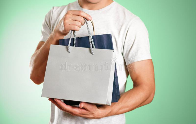 Man holding a blue and grey gift bags. Close up. Isolated background stock image