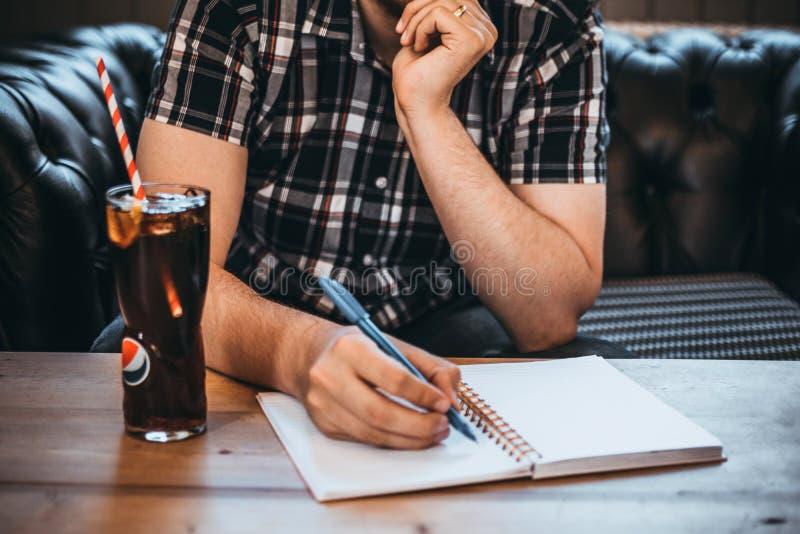 Man Holding Blue Pen Writing on White Notepad stock photography