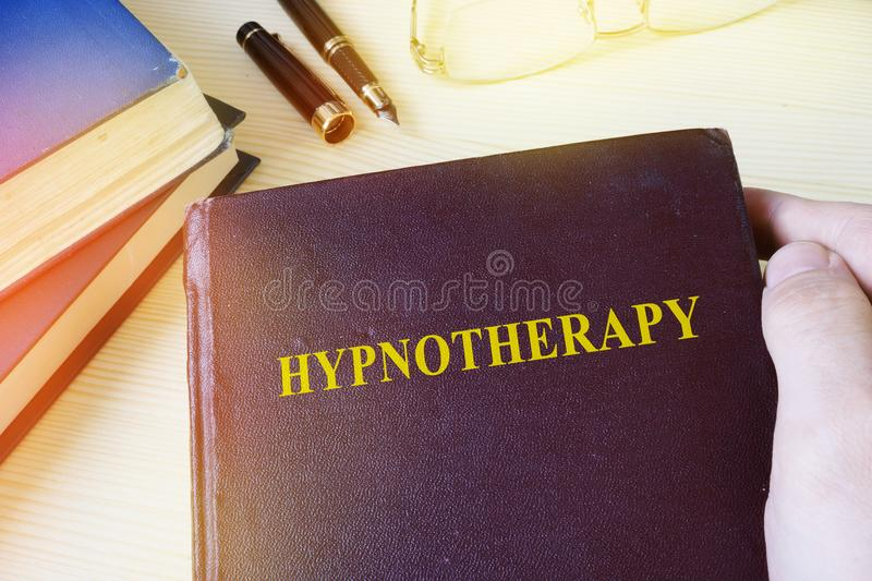 Man holding book with Hypnotherapy. stock photo