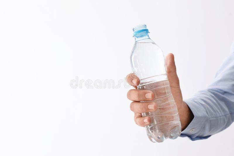 Man holding bottle of pure water on white background, closeup stock photography