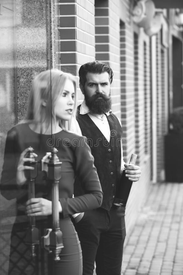 Man holding bottle of wine with woman opening glass door. Man holding bottle of wine with women opening glass door. Hipster with beard and girl in blue dress royalty free stock photo