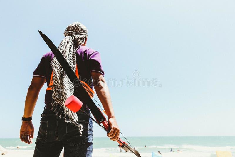 Man Holding Bow in Seashore stock photo