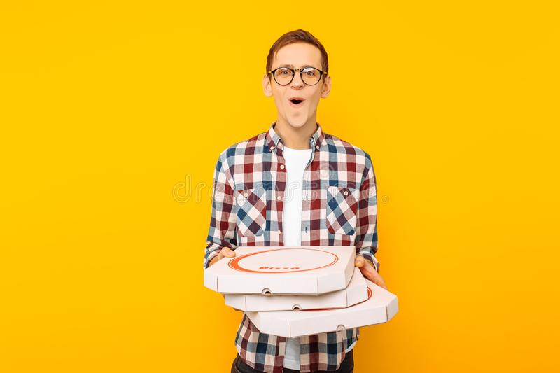 Man holding a box of pizza on a yellow background royalty free stock photography