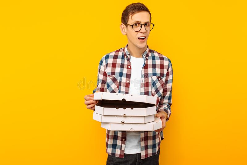 Man holding a box of pizza on a yellow background royalty free stock photos