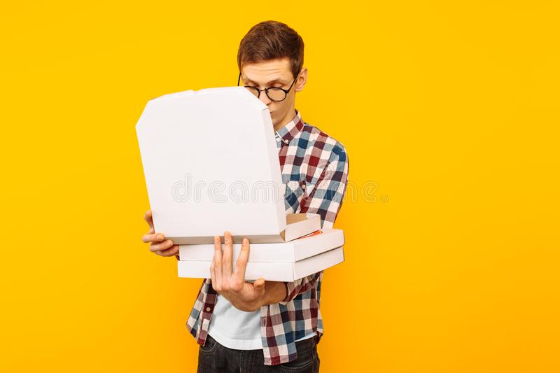 Man holding a box of pizza on a yellow background royalty free stock photo