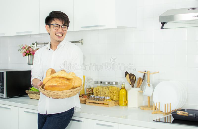 A man is holding breads in the kitchen. A cute man is holding breads and standing in the kitchen with happy royalty free stock images