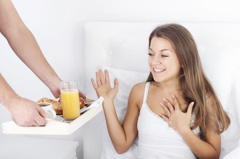 Man holding breakfast tray to woman in bed. Bedtime collection: man holding breakfast tray to woman in bed royalty free stock images