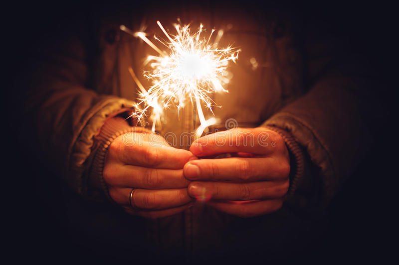 Man holding bright festive Christmas sparkler in hand, tinted ph. Oto royalty free stock photos