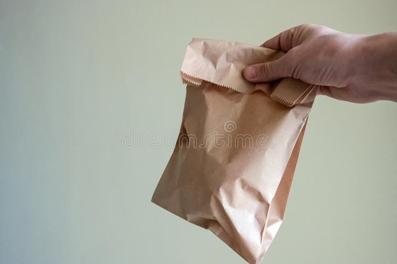 Man holding a brown paper bag with contents in his hand. Copyspace. Man holding a brown paper bag with contents in his hand. Copy space royalty free stock image