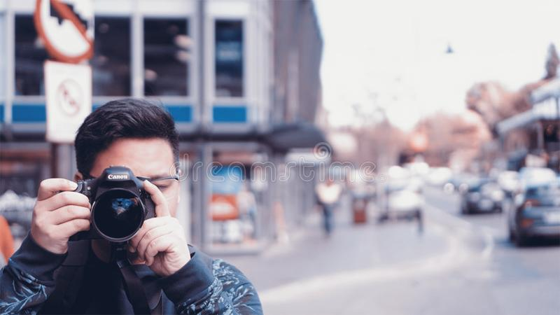 Man Holding A Camera On Busy Street stock photography