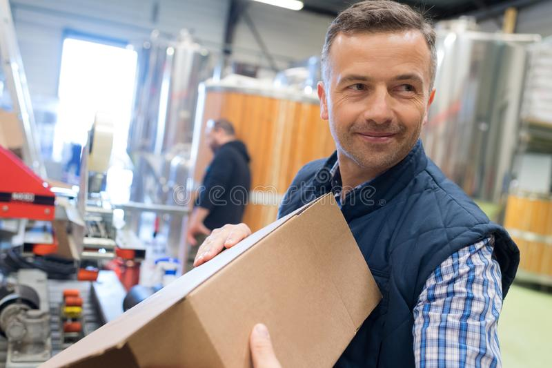Man holding cardboard box in factory dispatch department royalty free stock images