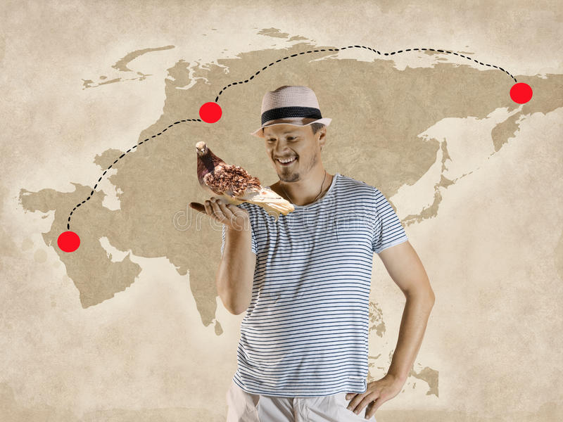Man is Holding a Carrier Pigeon. With Map Background-Mailing Concept royalty free stock image