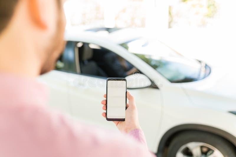 Man Holding Cellphone Against Car royalty free stock photos