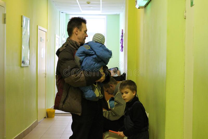 Man holding a child and children stand in line at the hospital receive benefits in a public institution waiting for admission royalty free stock photography