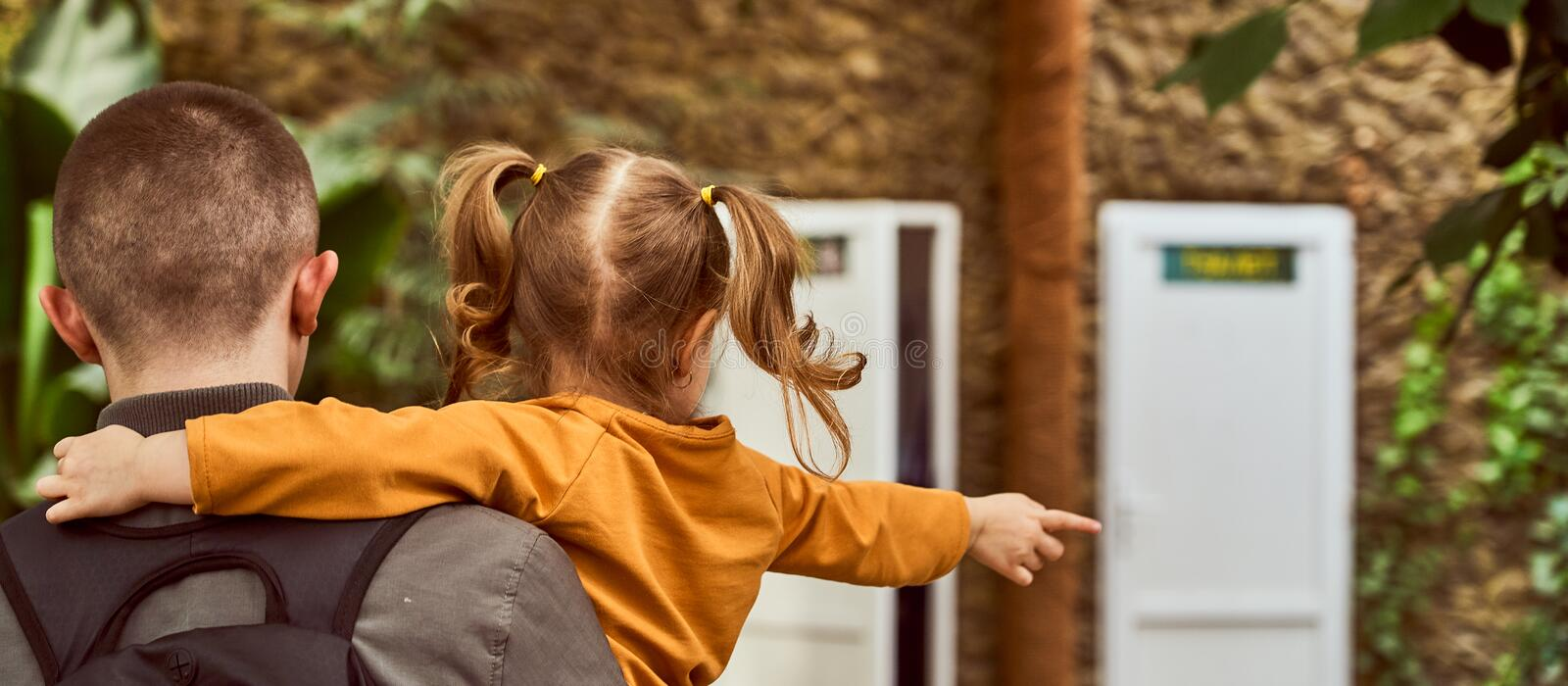 a man holding a child in his arms, back in the frame, go. royalty free stock image