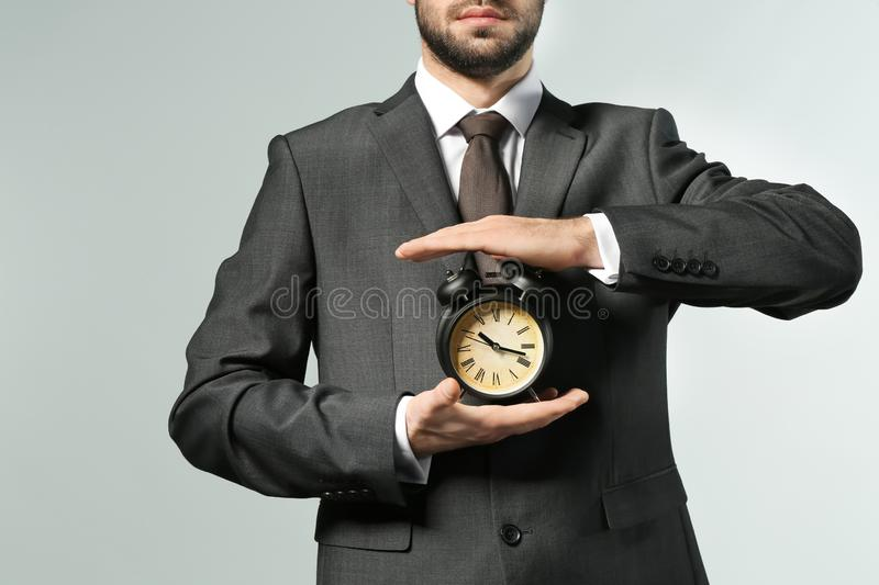 Man holding clock on grey background. Time management concept stock image