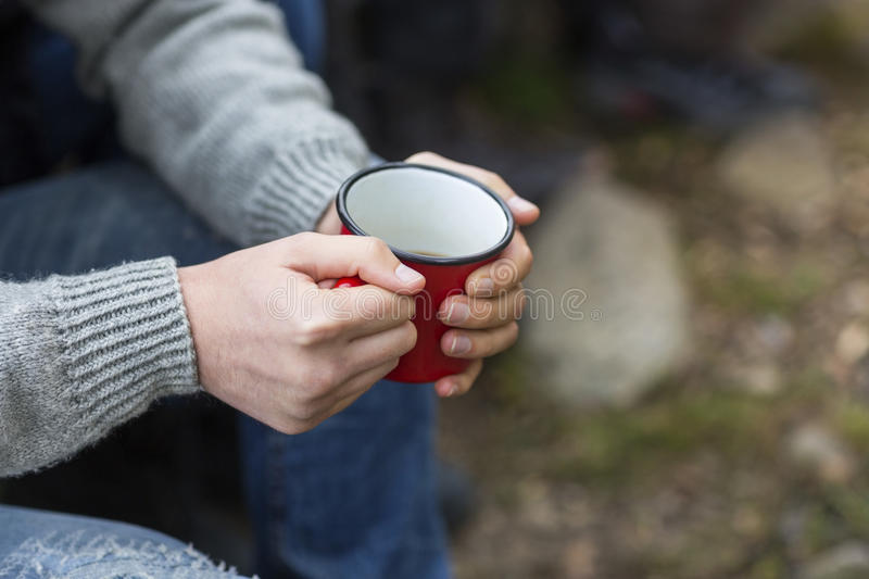 Man Holding Coffee Cup At Campsite. Midsection of young man holding coffee cup at campsite stock photography