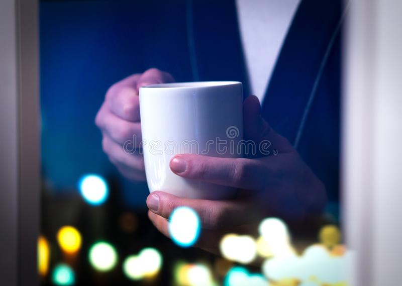 Man holding coffee cup by the window. Drinking tea or hot beverage. Insomnia or unable to sleep. Sick or having flu. Person stay awake late at night or wake up royalty free stock image