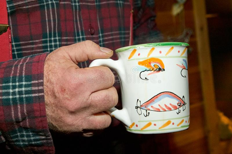 Man holding a coffee mug decorated with lures. Man holding a coffee mug decorated with freshwater fishing lures in a close up view against a plaid shirt stock photography