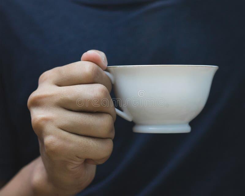 Man holding coffee mug in hand on dark shirt background. Vintage mugs for your design. Man holding coffee mug in hand on dark shirt background. Vintage mugs stock photos