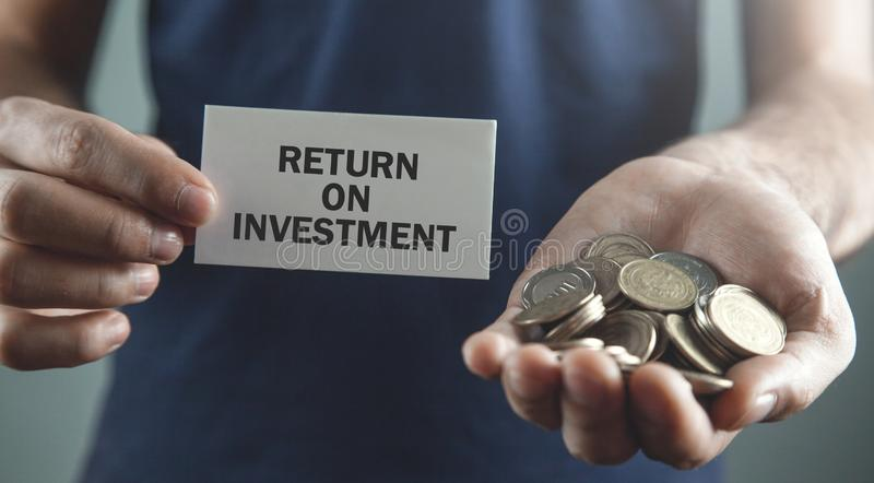 Man holding coins and business card. Return On Investment stock image
