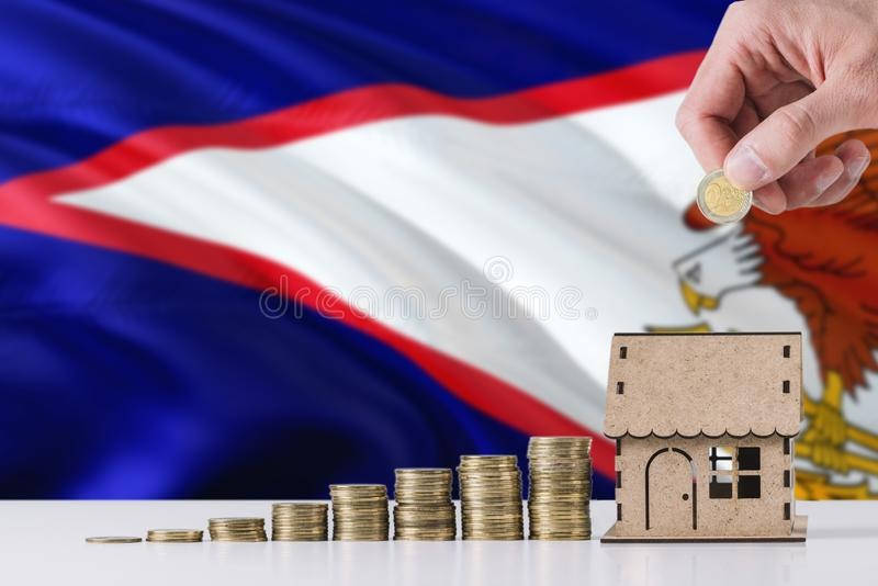 Man holding coins putting in wooden house moneybox, American Samoa flag waving in the background. Saving money for mortgage. Jar, savings, investment, earnings stock photos