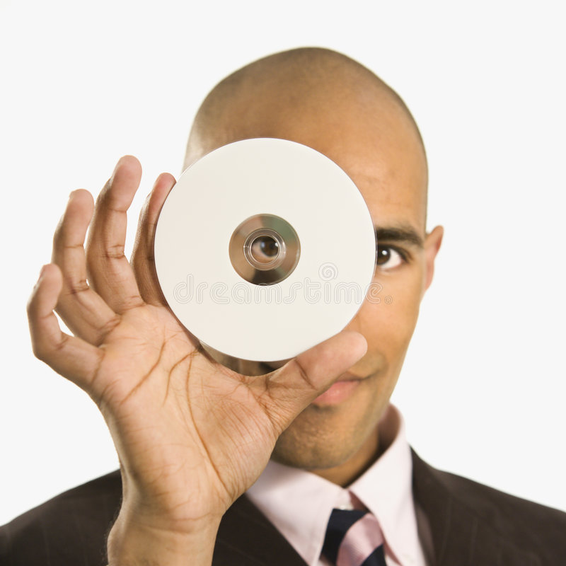 Man holding compact disc. African American man holding compact disc over face and peeking through hole royalty free stock images