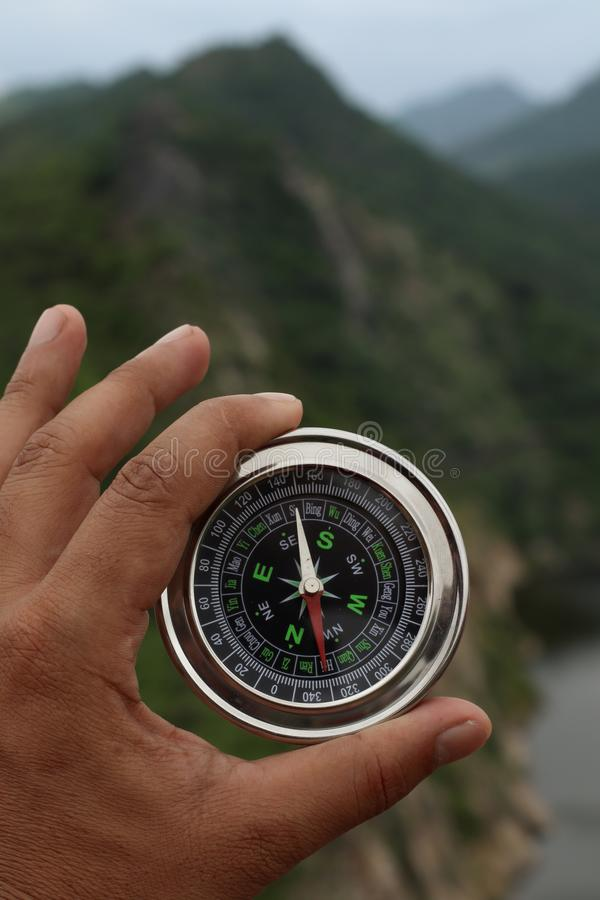 A man holding compass in his hand stock photo