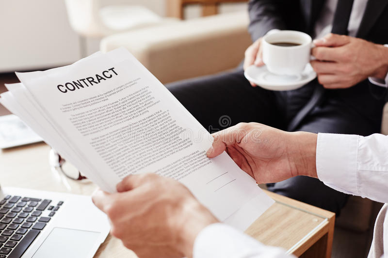 Man holding contract. Male employee holding contract and reading it royalty free stock image