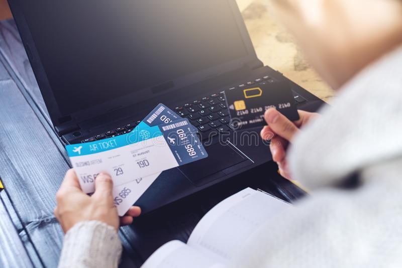 Man holding credit card and buys plane tickets on Internet. Man holding a credit card and buys plane tickets on the Internet working on the laptop. The concept royalty free stock images